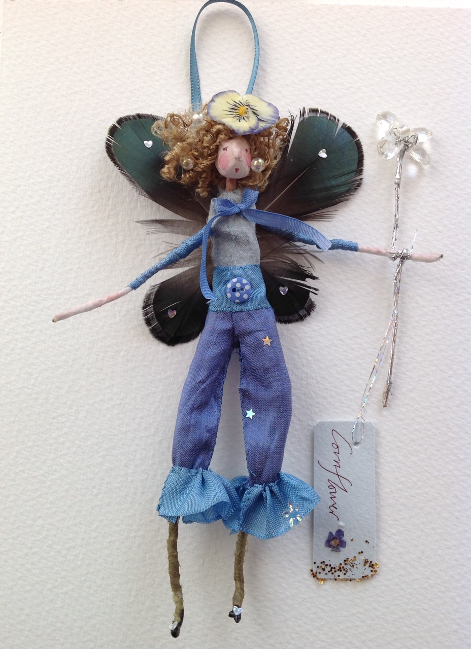 CORNFLOWER A 14cm fairy dressed in silk with peacock feather wings and a dried pansy headdress. £25 plus £3.50 p&p.