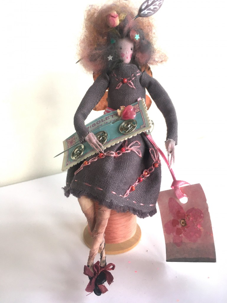 DELPHINE A 15cm high fairy who just loves to sew ! She is wearing a hand embroidered linen dress and she has silk painted butterfly wings. She is sitting on a large wooden cotton reel and on her lap she has a vintage French card of trees studs. Her fave is painted silk and her hair is brushed marino wool ( with a dried rosebud and leaf pin). £45 including UK postage ( add on £4 for international post).