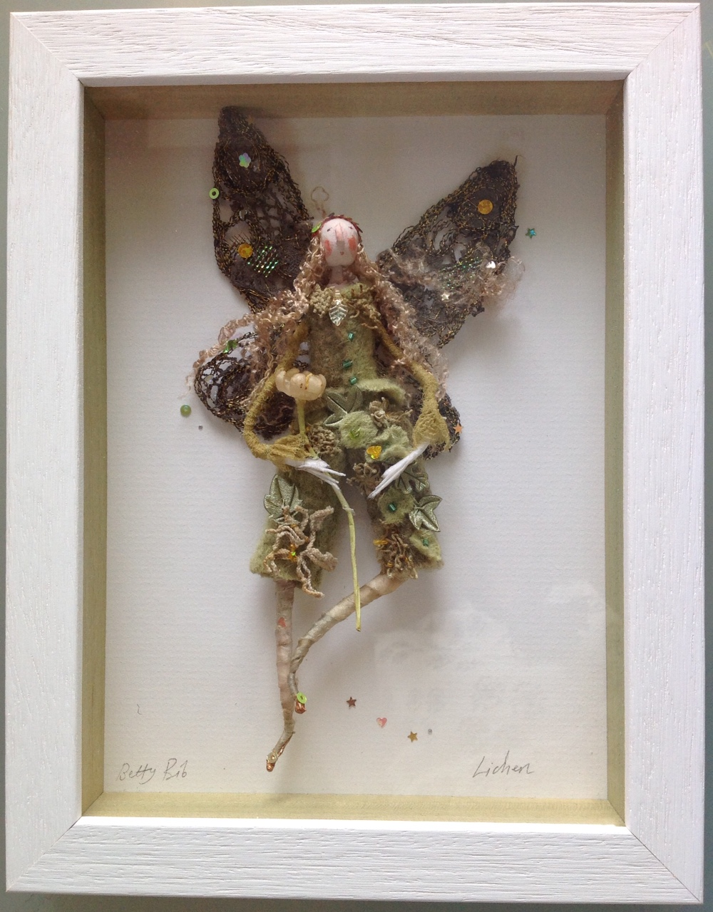 LICHEN; a 23x17.5 box framed fairy. Lichen is dressed in hand dyed ( with red onion ) clothes , trimmed with vintage lace. She has embroidered wings and is carrying a vintage wax flower. please e mail me if you would like to see her in more detail. £95 plus £3.50 postage.