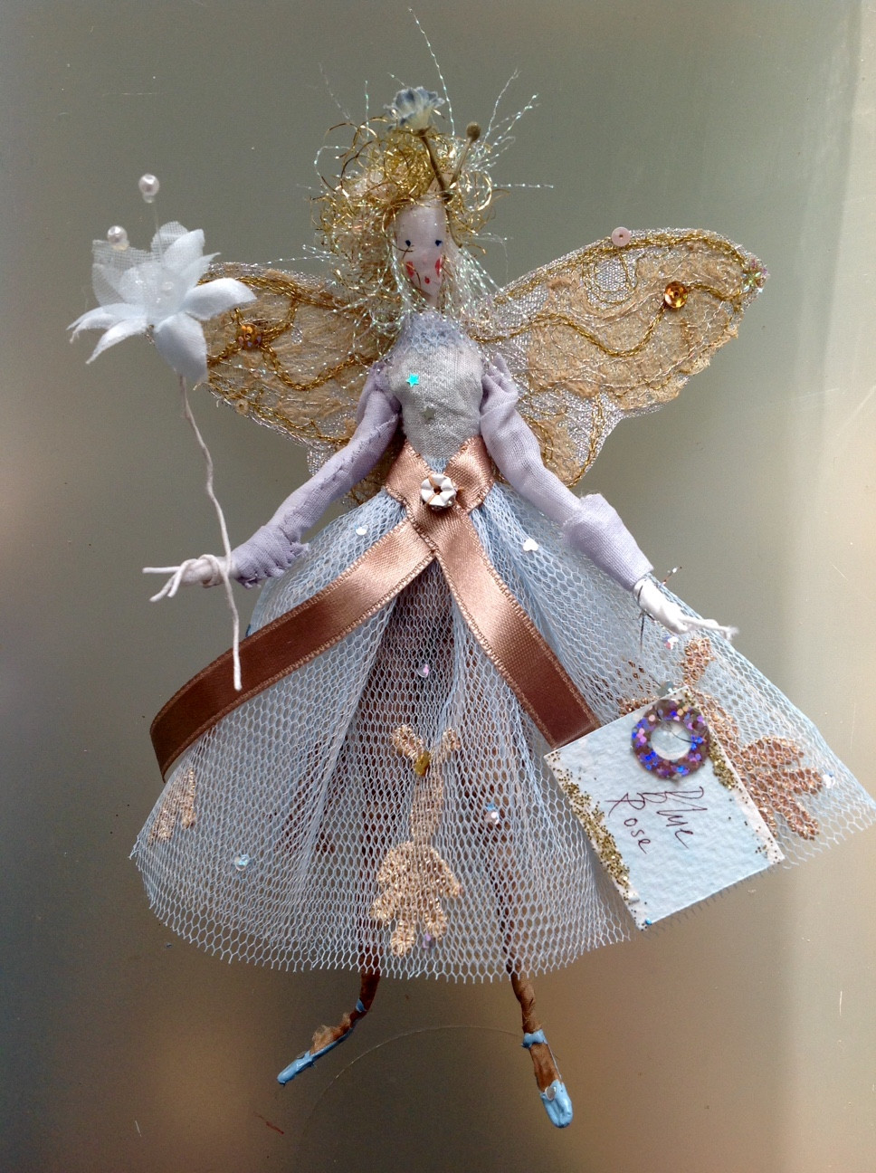 BLUE ROSE A 17cm high fairy wearing a and dyed silk and organdie top with a stiff net skirt embellished with brocade and sequins. Her wings are embroidered and she has a special flower sequin at the back of her waist. She comes in an organza bag with dried petals in it . £35 plus £3.50 p&p.