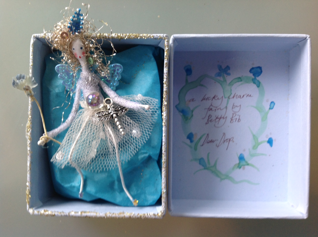 A LUCKY CHARM FAIRY A 9cm fairy in a box with a dragonfly charm at her waist. She is holding a paper flower wand. £20 plus £3.50 p&p