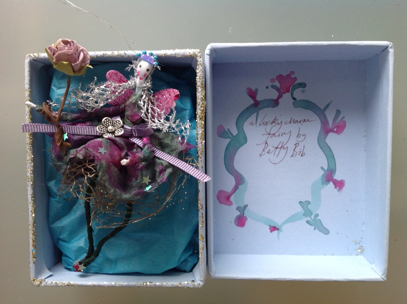 A LUCKY CHARM FAIRY  A 9cm fairy in a box with a flower charm at her waist. She is holding a paper rose wand. £20 plus £3.50 p&p