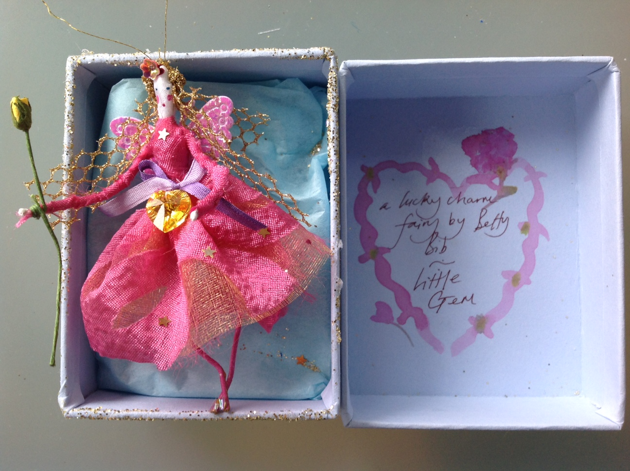A LUCKY CHARM FAIRY A 9cm fairy in a box with a very shiny heart stone at her waist. She is holding a paper rosebud. £20 plus £3.50 p&p