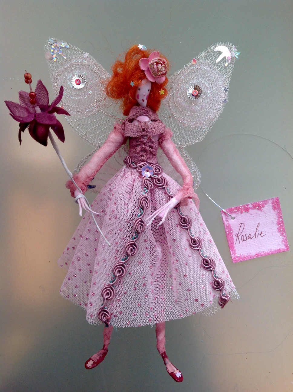 ROSALIE A 17cm high fairy with a a painted silk face . She is wearing a hand dyed top and stockings with a stiff glittered net skirt. She has a pink paper button at the back , embroidered wings , and a paper rose in her hair. She comes in an organza bag with dried petals in it. £35 plus £3.50 p&p