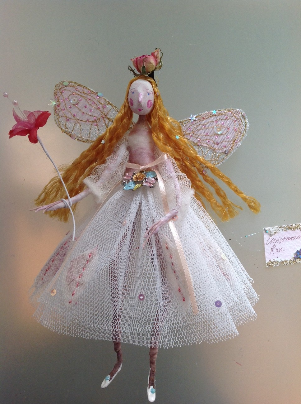CHRISTMAS ROSE A 20 cm high fairy with a paper clay painted face. She is wearing a felted top with fine tulle sleeves , a stiff net skirt embellished with felted leaves and sequins, with an enamelled jewel at her waist. Her wings are embroidered and she has a dried rosebud on her head. She comes in an organza bag with dried roses and petals in it . £48 plus £3.50 p&p