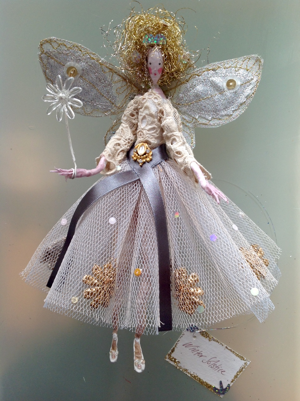 WINTER SOLSTICE A 20 cm high fairy with a painted silk face . She is wearing a vintage lace top and a stiff net skirt embellished with brocade and sequins with an Indian inspired jewel at her waist. Her wings are embroidered and she comes in an organza bag with dried flowers in it. £48 plus £3.50 p&p