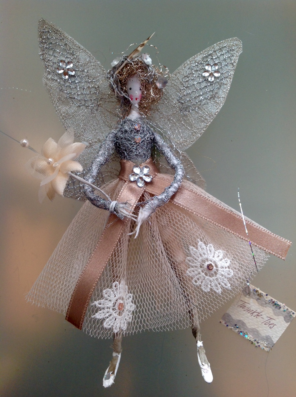 TWINKLE -TOES A 15cm fairy with a painted silk face , wearing a metallic lace top with a stiff net skirt embellished with lace flowers and sequins , her wings are embroidered and she has a tiny quail's feather in her hair. She comes in an organza bag with dried petals in it. £30 plus £3.50 p&p.