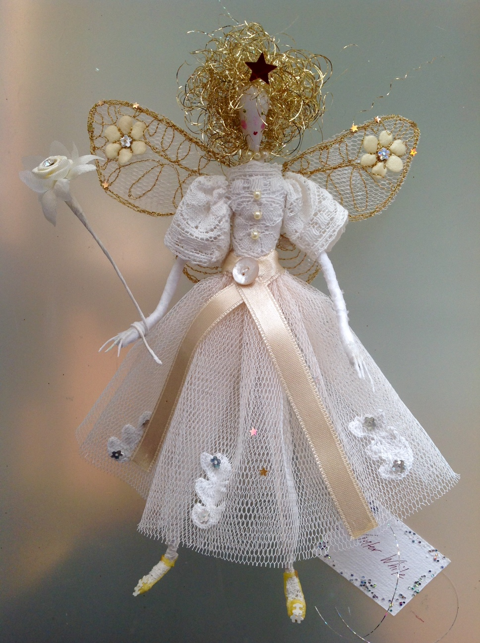 WINTER WHITE A 21cm fairy with a silk painted face , wearing vintage lace and a stiff net skirt embellished with lace and sequins. She has embroidered wings , an orange/gold star in her hair and she is holding a diamante flower wand. She comes in an organza bag with dried flower petals in it. £45 plus £3.50 p&p.