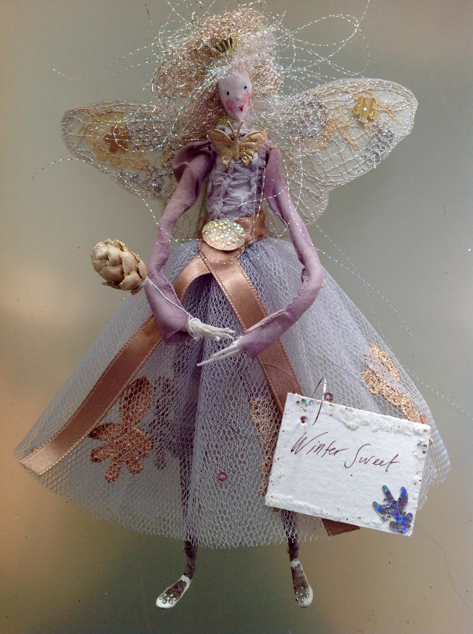 WINTER SWEET A 21cm high fairy . She has a painted silk face and embroidered wings, a stiff net skirt and hand dyed top and stockings ... all embellished with brocade and sequins . She has a pearl button at the back and is carrying a dried Alder cone wand.She comes in an organza bag with dried petals in it. £45 plus £3.50 p&p
