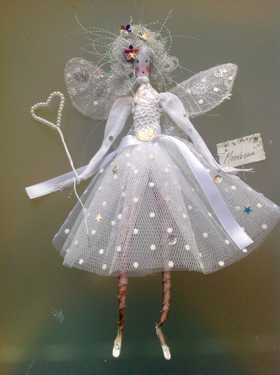 MOONBEAM , a 22cm fairy wearing a vintage lace and cotton organdie top with a stiff net and spotted flocked skirt. She has a sparkly jewel at her waist, has embroidered wings and is holding a pearl wand.She comes in an organza bag with dried flower petals in it . £40 plus £2.50 p&p