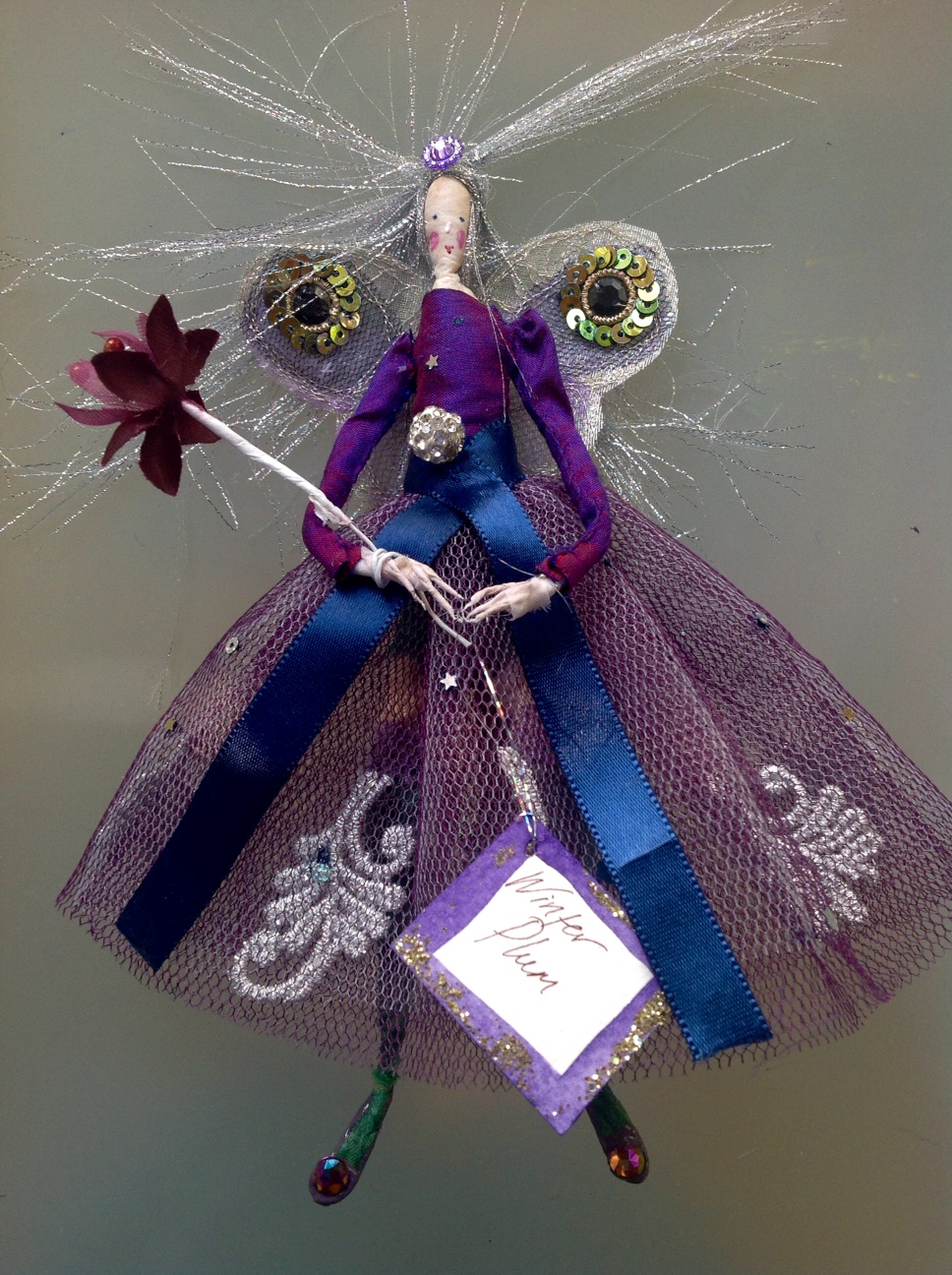 WINTER PLUM, a 17cm fairy with a silk painted face , a shot silk top and stiff net skirt embellished with silver brocade and sequins. This cheeky fairy has green silk stockings and matching knickers. She comes in an organza bag with dried flower petals. £40 plus £2.50 p&p