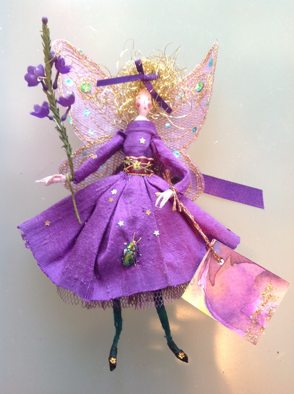 AMETHYST, a 15cm fairy with a silk painted head . She is wearing a shot silk dress with satin ribbons and an iridescent glass beetle. She has stiffly embroidered wings and is holding a spray of fabric flowers. She comes in an organza bag with dried petals and her painted name tag. £25 plus £2 postage.