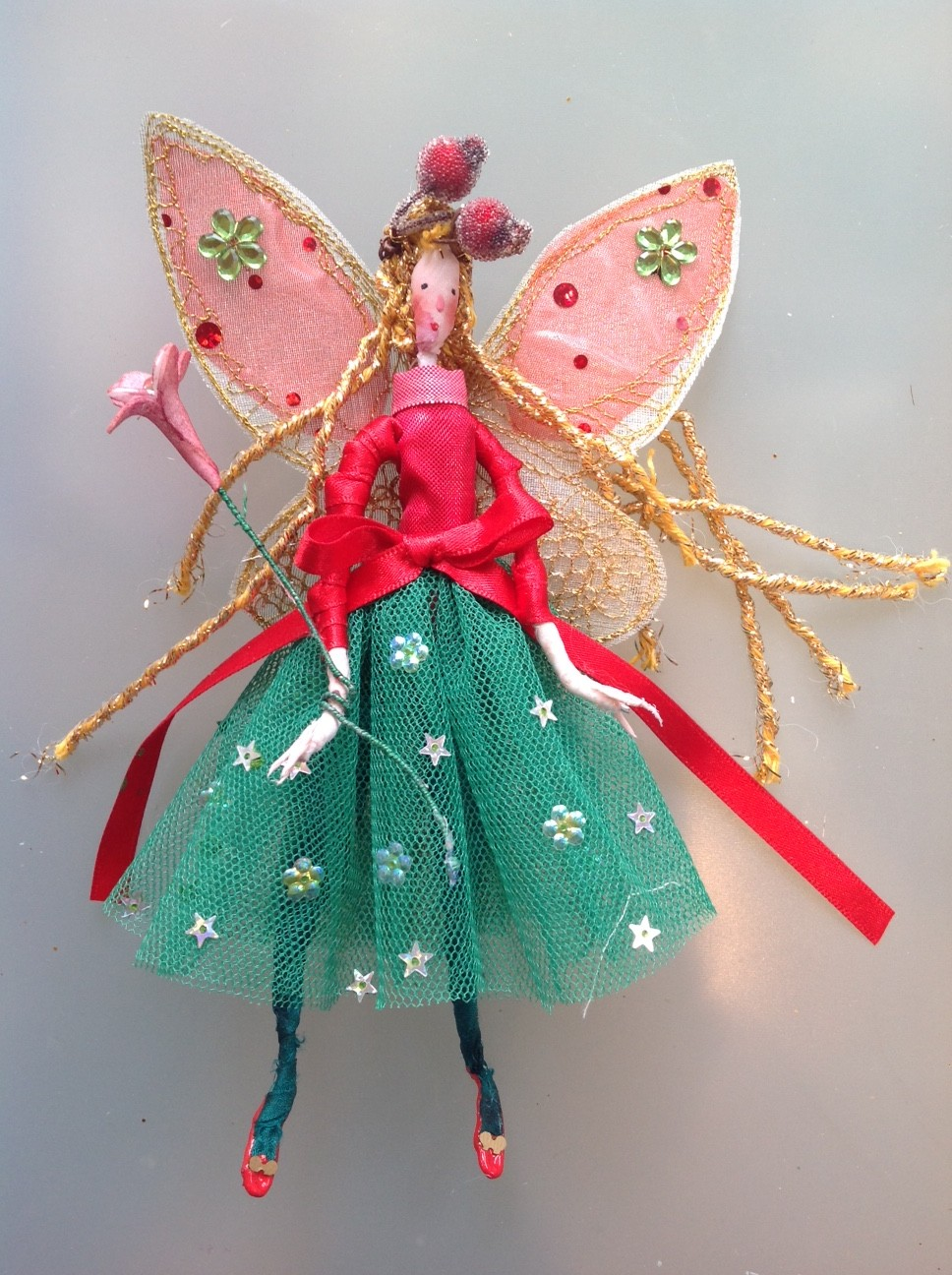 HOLLY BERRY, a 17cm fairy with a silk painted face. She is wearing a stiff net skirt with a shot metallic top and a satin ribbon at the waist. She has stiffly embroidered wings and has frosted berries in her hair. She comes in an organza bag with dried petals and a hand painted name tag. £25 plus £2 postage.