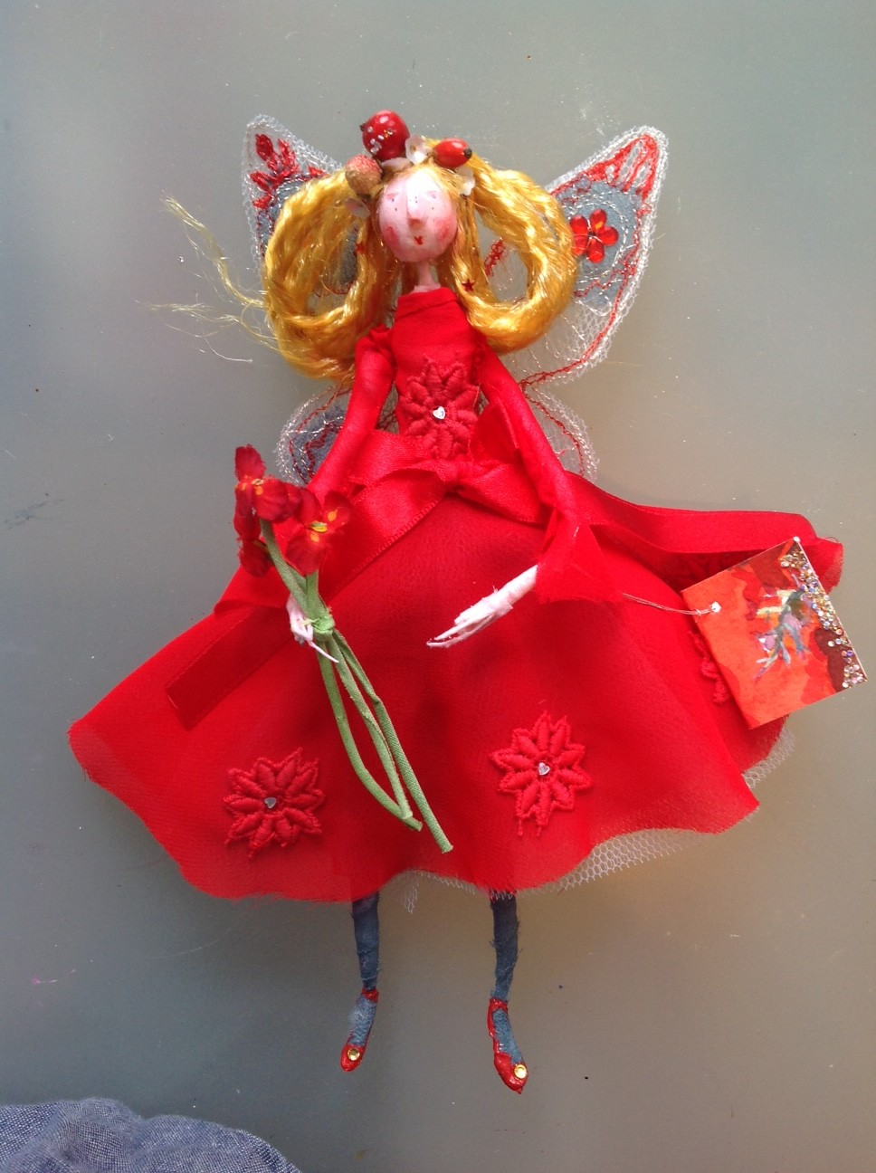 RUBY RED, a 20cm fairy with a painted clay head. She is wearing a bright red very floaty chiffon dress embellished with cotton flowers with iridescent hearts. She has stiffly embroidered wings , has berries in her hair and is holding vintage fabric flowers. She comes in an organza bag with dried petals and her hand painted name tag. £40 plus £3 postage.