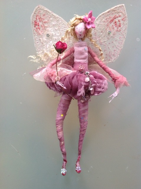 Raspberry Ripple. A 17cm high fairy with a paper clay head and embroidered wings. Her dress is made of crushed velvet and chiffon and is decorated with a droplet jewel . She is also wearing cranberry dyed silk stockings and is holding a paper rose wand ( she also has a large organza bow at her back. She comes in an organza bag with dried petals . £38 plus £3 p&p