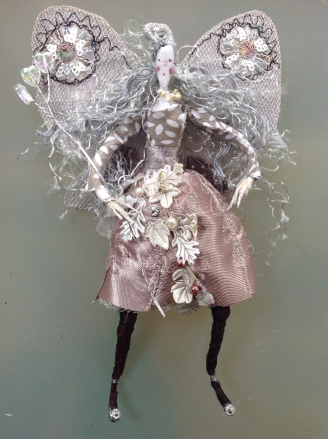 Sylvia A 17cm fairy with a silk painted head. She has stiff embroidered wings and is wearing a cotton and shiny satin dress decorated with pearls and satin leaves. She has a wired organza bow at her back. She comes in an organza bag with dried petals. £40 plus £3 p&p