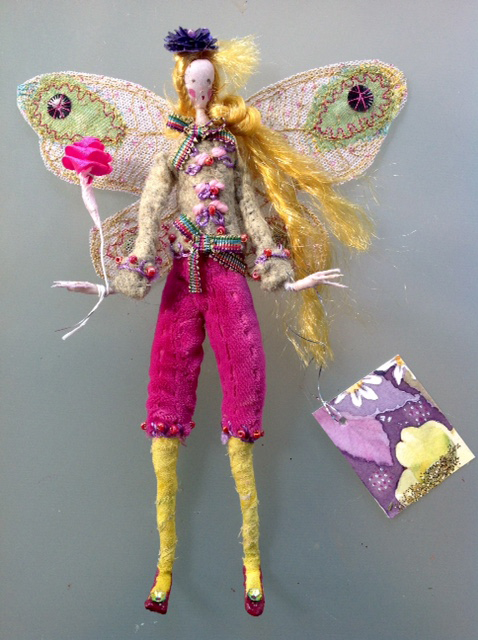 GRETCHEN; A 16 cm fairy with a hand painted silk face - she is wearing a hand embroidered and beaded felt jacket and silk velvet breeches. She is holding a satin ribbon rose and has stiffly embroidered wings ( transparent in the light ) and a purple sequinned hat. She comes in an organza bag with a hand painted name tag. £35 plus £2 postage