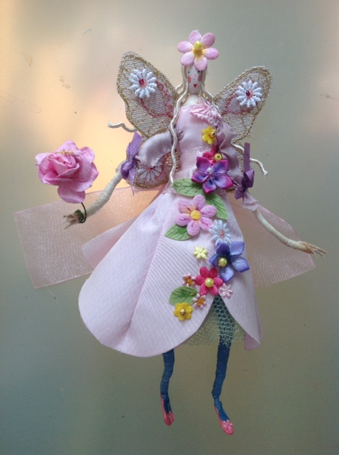 An 18cm fairy with a painted silk head, dressed in a stiff pink taffeta dress decorated with hand painted flowers and beads. This fairy has embroidered net wings and is carrying a paper rose . She comes in an organza bag with dried petals in it and a painted name tag. £45 plus £3 p&p
