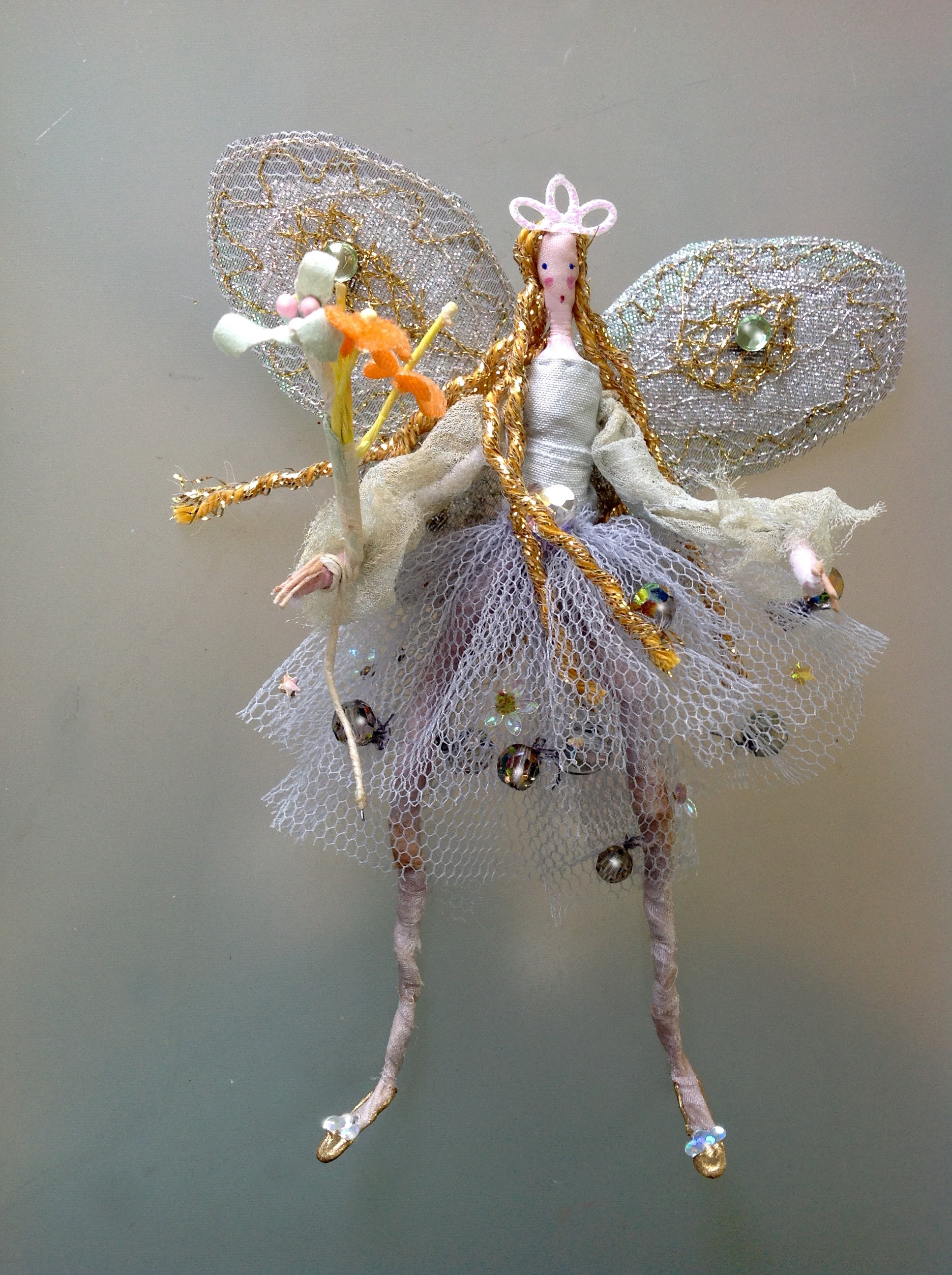 CRYSTAL An 11 cm high fairy wearing a hand dyed chiffon top and stiff netted skirt embellished with crystals and a special heart crystal at her waist. She has stiffly embroidered wings and is carrying a fabric and paper flower wand. She comes in an organza bag with dried petals. £28 plus £2 p&p.