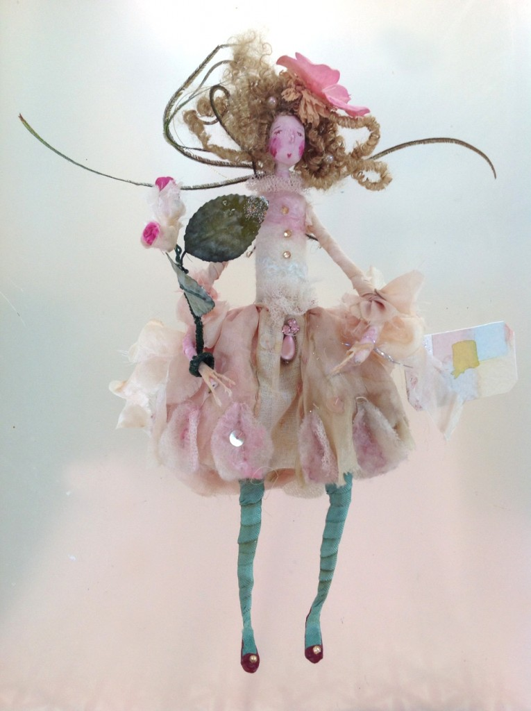 ROSAMUND A 19cm high fairy with a paper clay head.She is dressed in hand dyed silk and felted silk and her dress is embellished with vintage tulle , gems and sequins. Her wings are Peacock feathers and her wand is paper and silk rose buds. She comes in an organza bag with dried petals and a hand painted name tag. £ £40 plus £2 p&p