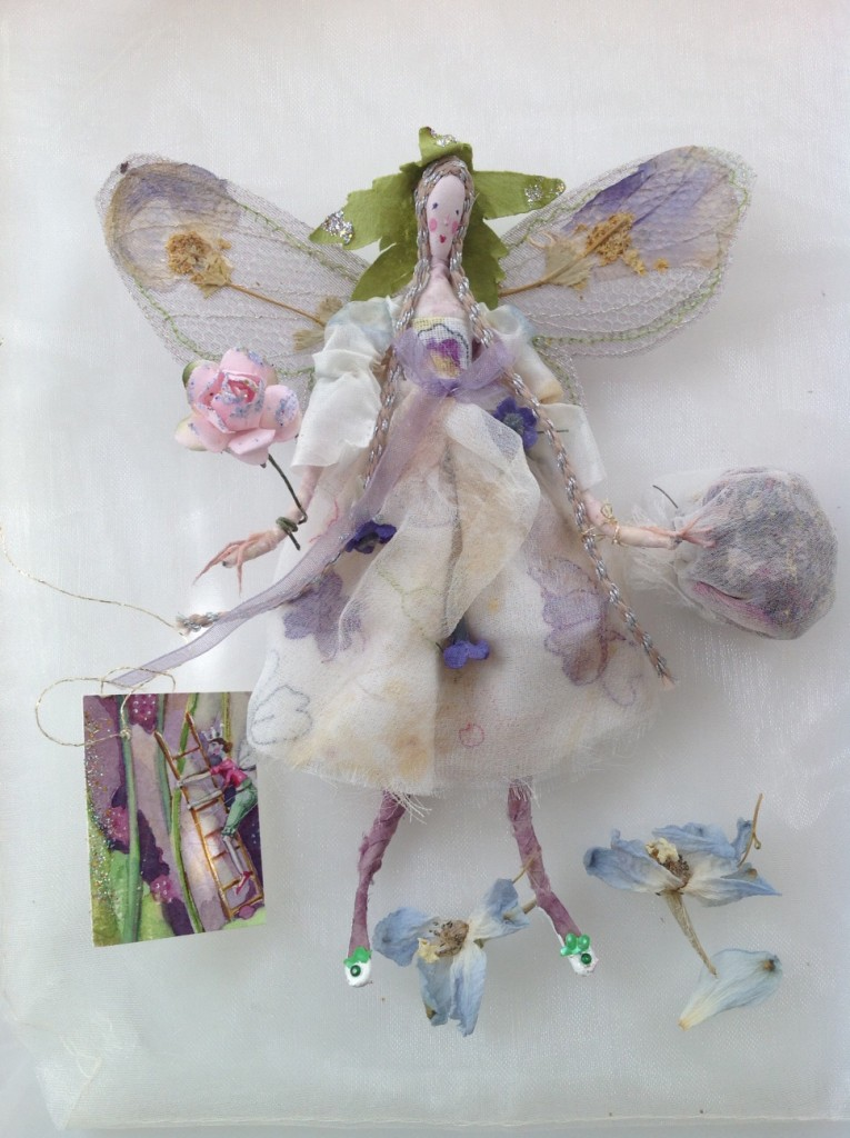 MILLEFIORE; A 15cm high fairy with a silk painted head.She is dressed in eco - printed ( impressions of verbena flower heads ) and embroidered silk chiffon. Her wings are stiffly embroidered and her wand is a paper rose. She is holding a chiffon bag of sweet smelling potpourri and she comes with a hand painted name tag and an organza bag with dried petals. £40 plus32 p&p