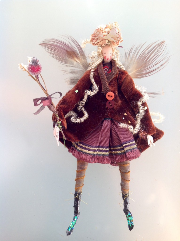 WINTER BERRY A 16cm high fairy wearing a silk velvet coat with a pleated and fringed skirt . She has pheasant feather wings , a dried rose hat and is holding a dried flower and crystallised berry wand. She comes with a hand-painted name tag and in an organza bag with dried flowers. £42 plus £3.50