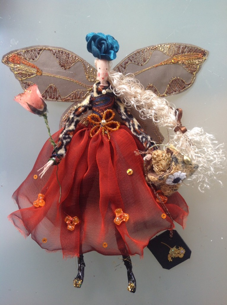 GALA, a 17cm high fairy with a silk painted head. This fairy is wearing a leopard skin long sleeved bolero over a paisley top and she has a chiffon and net skirt. She has a beaded flower at her waist , stiffly embroidered wings and is holding a wooden bag with a glittered alder cone inside it. She also has a fabric rose wand and a satin rose hat and a dried flower name tag. She comes in an organza bag with dried flowers in it. £40 plus P&P.