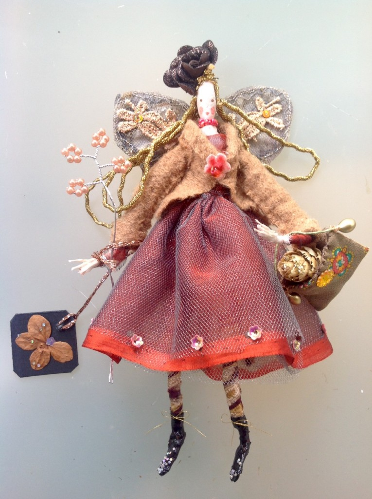 GIGI, a 17cm high fairy with a silk painted head and wearing a chiffon and fine tulle dress. She has patterned tights and patent boots. Her winter jacket is fine felted wool and has a velvet flower button. She has stiffly embroidered wings and she is holding a silk bag with a glittered alder cone inside it . She is also holding a pearl wand and a dried flower name tag. Her hat is a fabric rose. Gigi comes in an organza bag with dried flowers. £40 plus £3.50 p&p.