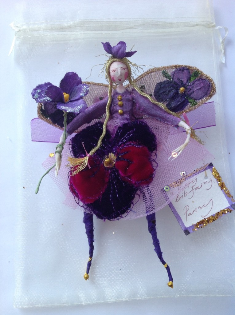 A 13cm high fairy with a clay painted head . She is wearing a velvet pansy embroidered skirt with a silk top. Her wings are stiffly embroidered with violas and she is holding a vintage violet and has an organza bow at her back. She comes in an organza bag with dried flowers. £38 plus £3.50 postage.
