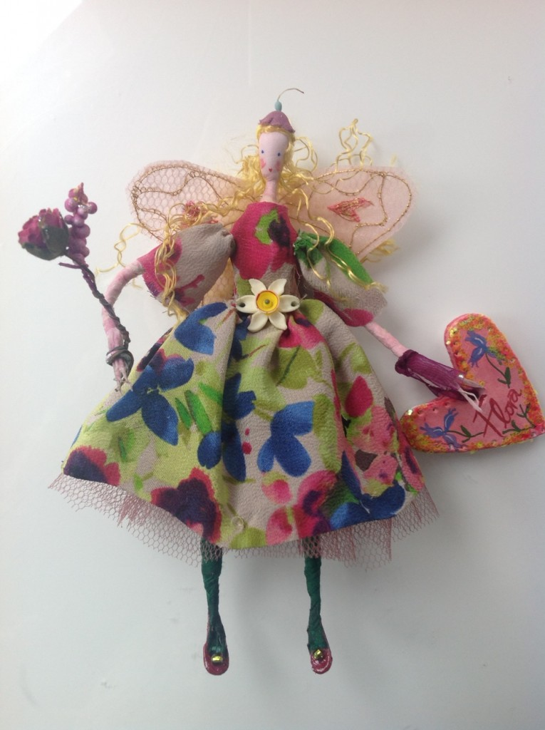 FLORA A 14cm Lonely Heart fairy with a silk painted head. She is wearing a silk crepe dress with a vintage narcissus flower at her waist and stiff net underskirt ... her wings are embroidered organza and she is holding a paper flower bouquet and a painted clay name tag. £27 plus £2 p&p.