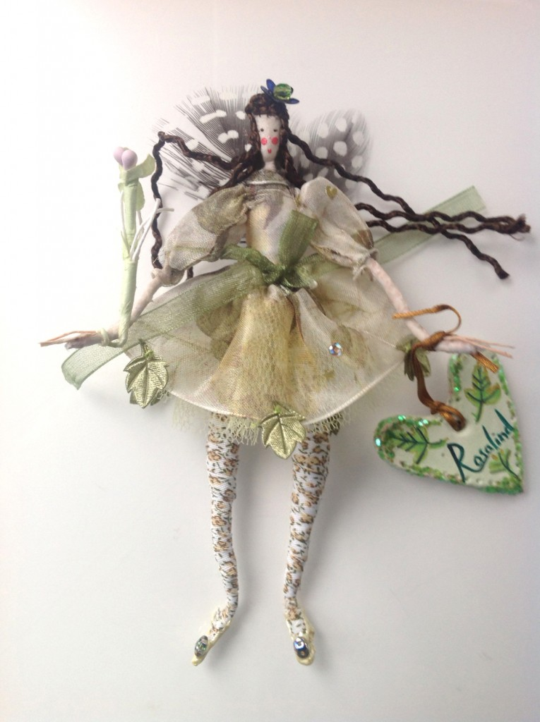 ROSALIND A 14cm Lonely Heart fairy with a silk painted head and guinea fowl feather wings. Her dress is printed organza with an organza ribbon and she has a sparkly flower in her hair. She is holding a paper flower wand and her name tag is made of clay £27 plus £2 p&p.