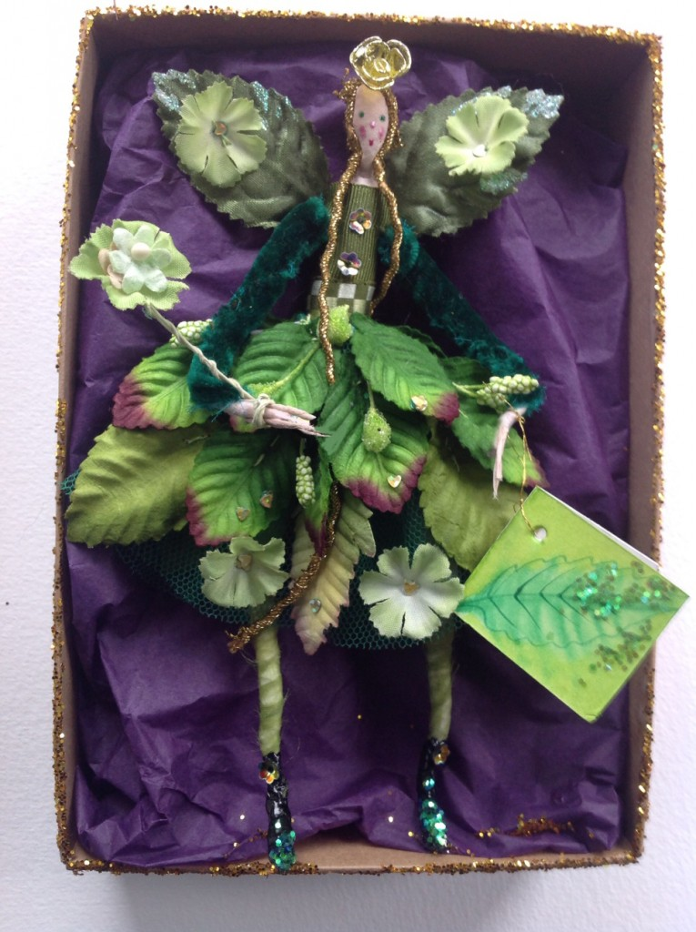 GREENSLEEVES A 15cm high fairy with a silk painted head. This Spring fairy is wearing a stiff net skirt with paper leaves, flowers, sequins and crystallised berries sewn on to it . She has silk velvet sleeves and a hand painted name tag. She comes in a Betty Bib box. £32 plus £3.50 p&p.