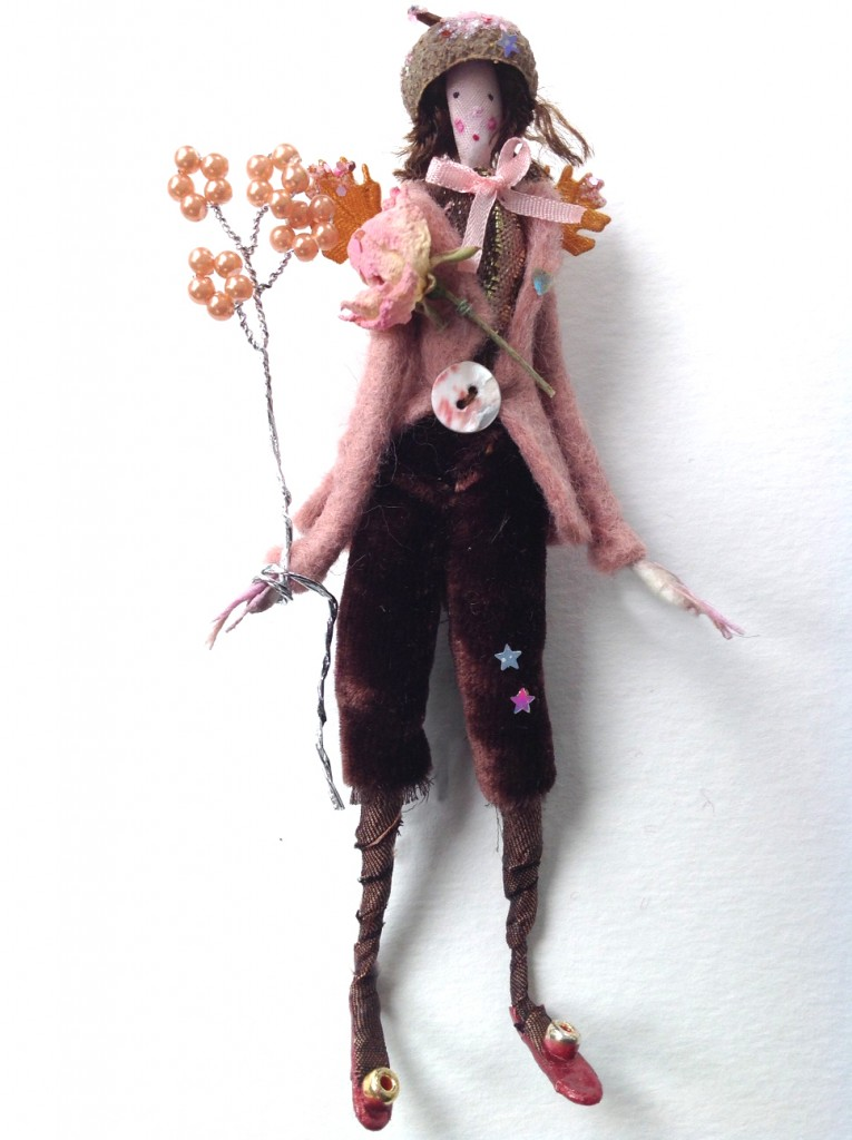 TEA-ROSE A 12cm high fairy wearing a felted coat with pearl button, silk velvet breeches and a brocade top . Tea-Rose has a dried rose buttonhole , tiny glittered wings, a pearl wand and a glittered acorn cup hat. She/he comes in a 15cm long box , decorated with dried flowers from my garden and is a numbered limited edition.( Number 1) £40 plus £3.50 postage