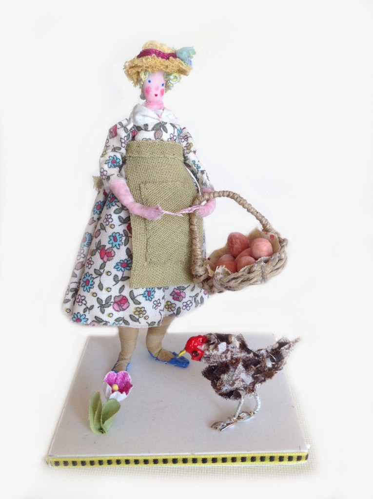 A 12cm high figure on a ribbon edged foam board base . Dolly is holding a handmade basket with clay eggs and has a fabric chicken pecking at her feet. £50 including UK postage ( please email me for international postage).