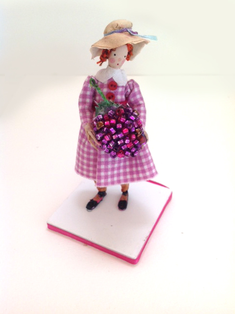 A 10cm high figure with a silk painted head standing on a foam board base , edged with ribbon. She is holding a beaded raspberry.