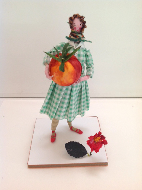 A 13 cm high figure with a silk painted head , standing on a ribbon edged foam board base. She is wearing a cotton frock with tiny buttons and a silk headscarf. Her oversized tomato is painted silk and there is a paper flower at her feet. £50 including UK postage ( please email me for international postage).