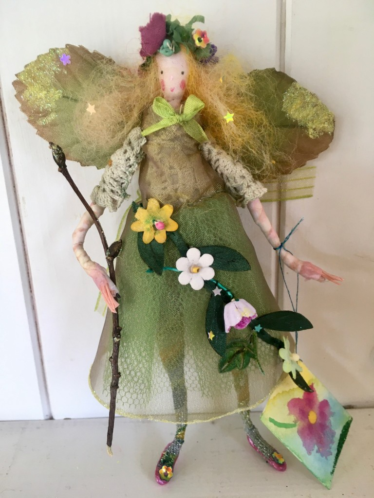 SWEET MAY A 13cm high fairy with a silk painted face. This little Spring fairy is wearing a vintage cotton crochet top overlaid with a shot organza dress with a glittered hem. She has a paper and fabric flower garland embellished with sequins , an organza bow at her back and is holding a glittered twig. She comes with a hand painted name tag and in an organza bag. £35 including UK postage.