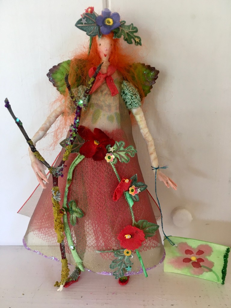 MAY- RED A 13cm high fairy with a silk painted face. This little Spring fairy is wearing a vintage cotton crochet top overlaid with a shot organza dress with a glittered hem. She has a paper and fabric flower garland embellished with sequins , an organza bow at her back and is holding a glittered twig. She comes with a hand painted name tag and in an organza bag. £35 including UK postage.
