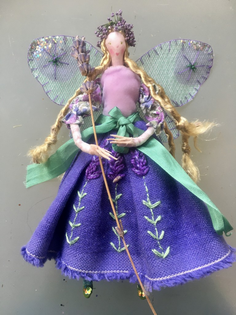 LAVENDER , a 15cm high fairy with a hand embroidered linen skirt tied with a silk ribbon. She has a Liberty print sleeved top with a velvet bodice. her wings are embroidered , stiff organza . She has a dried lavender wand and comes in an organza bag with a hand painted name tag. SUMMER SALE £28 including UK postage .