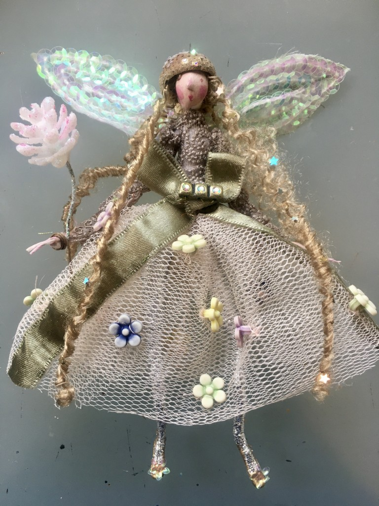 A 15cm high fairy with a dried Acorn cup hat . She is wearing a fine French lace top and her wings are encrusted with sequins . Her skirt is net and decorated with floral buttons. She is holding a glittered pine cone. SUMMER SALE £28 including UK postage .